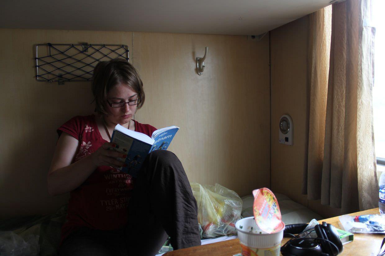 Samantha reading about Hanoi on the sleeper train