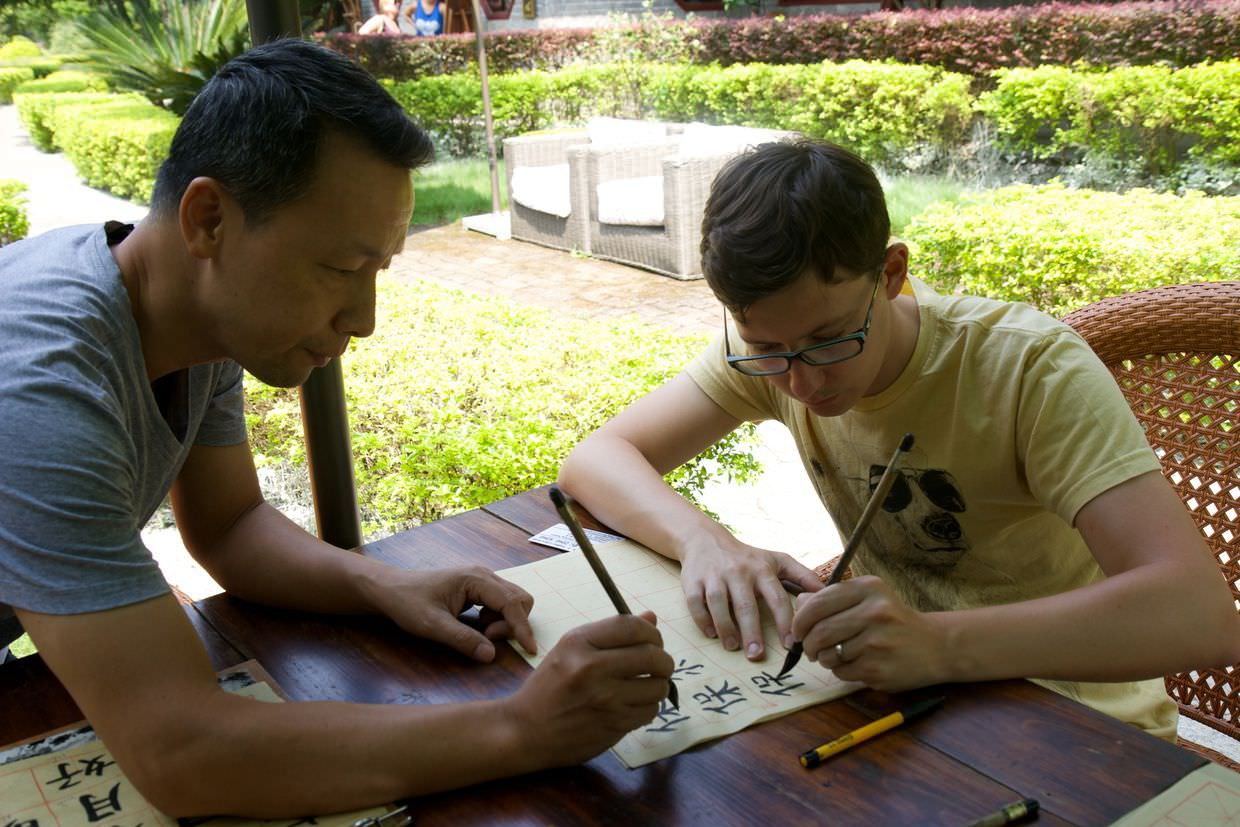 Zeng Song teaching Paul to write his name