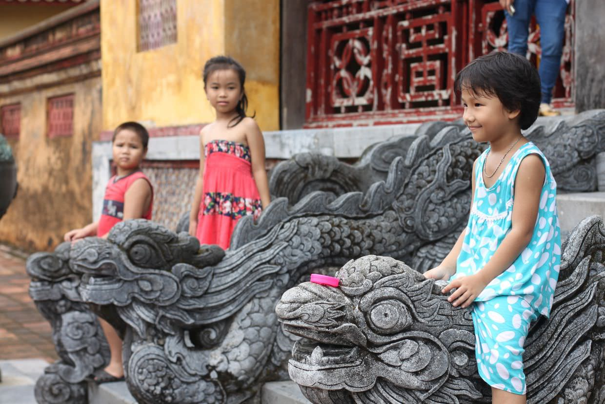 Children playing on the stone dragons