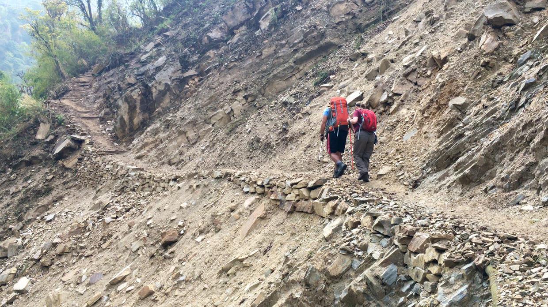 Sam and Big D walking across a recent landslide
