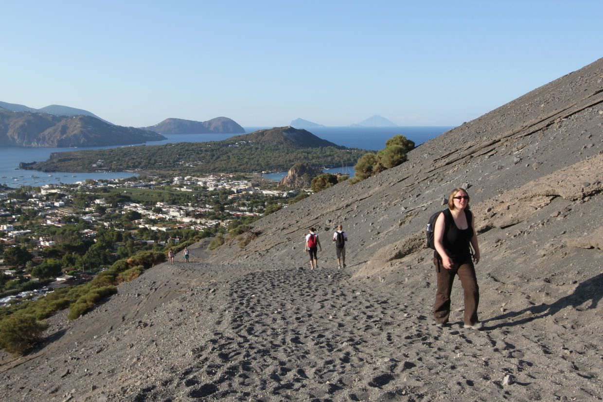 Samantha struggling on the Volcano, with the town and Lipari behind