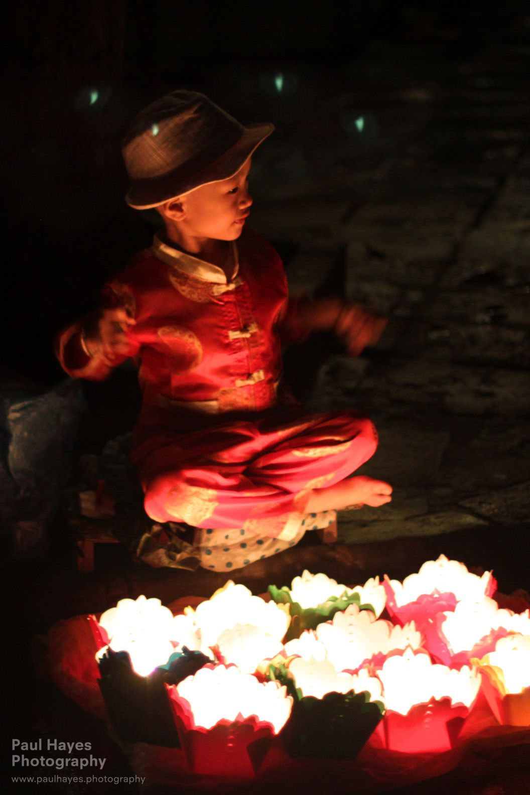 A child selling lanterns, sitting with the faeries